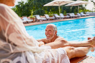 Happy couple relaxing at sunny resort swimming pool - CAIF23181