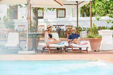 Mature couple relaxing on lounge chairs at resort poolside - CAIF23190