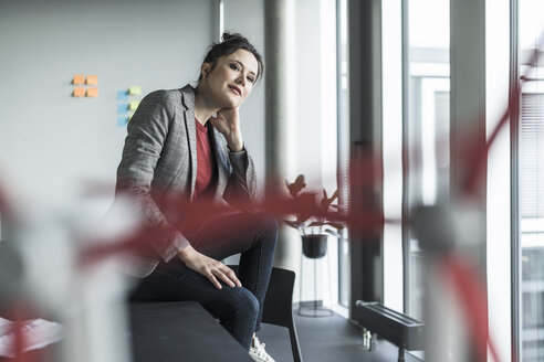Portrait of businesswoman sitting on desk in office - UUF17086