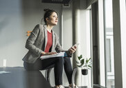 Businesswoman sitting on desk in office looking out of window - UUF17089