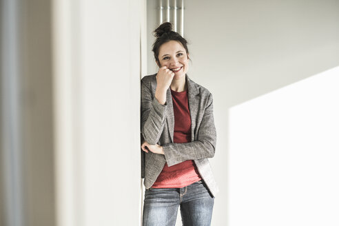 Portrait of smiling businesswoman leaning against a wall in office - UUF17098