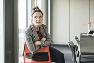 Portrait of businesswoman sitting on chair in office looking sideways - UUF17101
