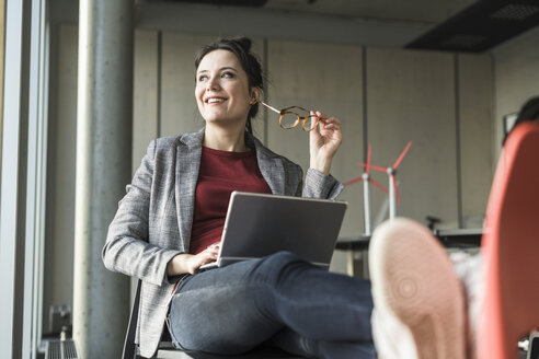Smiling businesswoman sitting on chair in office with laptop looking sidways - UUF17104