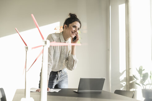 Businesswoman with wind turbine models and laptop on desk in office talking on cell phone - UUF17110