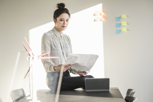 Businesswoman in office reading plan with wind turbine models on desk - UUF17113