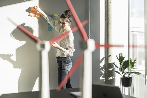Businesswoman in office putting sticky notes on wall with wind turbine models on desk - UUF17116