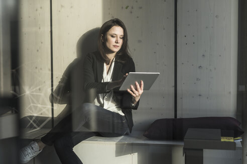 Businesswoman with tablet sitting in lounge area in office - UUF17125