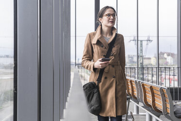 Smiling businesswoman walking with baggage and cell phone - UUF17134