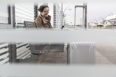 Smiling businesswoman with baggage sitting at station looking at cell phone - UUF17137