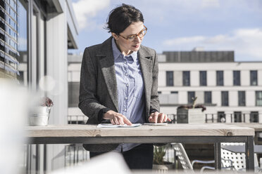 Businesswoman using cell phone on roof terrace - UUF17143