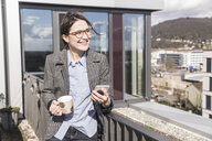 Smiling businesswoman with cell phone and cup of coffee on roof terrace - UUF17146