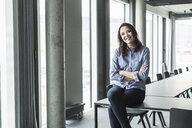 Portrait of smiling businesswoman sitting on conference table in office - UUF17155