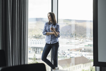 Businesswoman with cell phone standing at the window in office - UUF17158