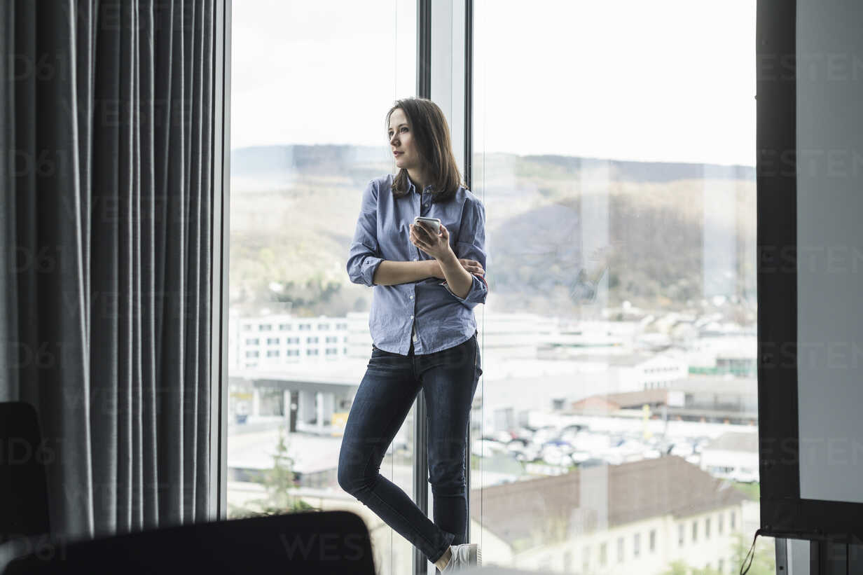 Businesswoman with cell phone standing at the window in office - UUF17158 - Uwe Umstätter/Westend61