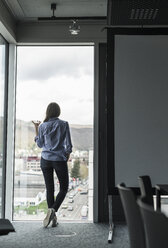 Rear view of businesswoman with cell phone standing at the window in office - UUF17161