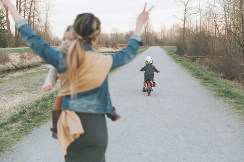 Mother carrying daughter and cheering her little son, riding bicycle - CMSF00044