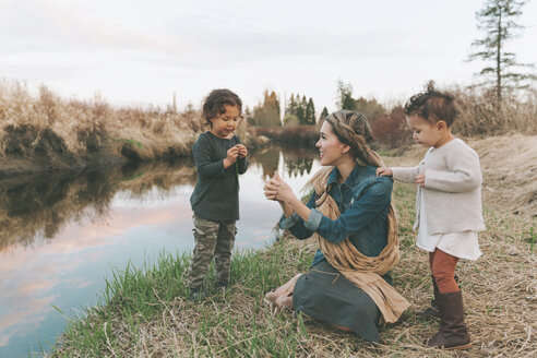 Maother and children playing with a grass blade at a river - CMSF00050
