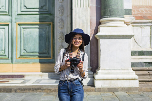 Italy, Florence, portrait of happy young tourist with camera - MGIF00332