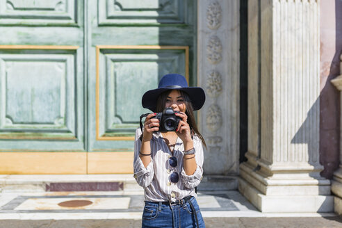 Italy, Florence, portrait of smiling young tourist taking photos with camera - MGIF00335