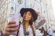Italy, Florence, Piazza del Duomo, portrait of happy young tourist taking selfie with smartphone - MGIF00350