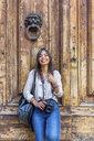 Italy, Florence, portrait of happy  tourist with camera and backpack standing in front of wooden door - MGIF00353