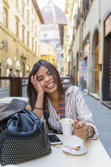 Italy, Florence, portrait of happy young tourist drinking espresso at pavement cafe - MGIF00356