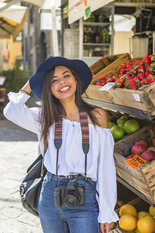 Italy, Florence, portrait of happy young tourist with camera standing in front of a grocery - MGIF00359