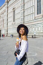 Italy, Florence, Piazza del Duomo, happy young tourist with camera and  ice cream cone - MGIF00362