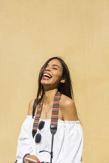Portrait of laughing young woman in front of yellow background - MGIF00368