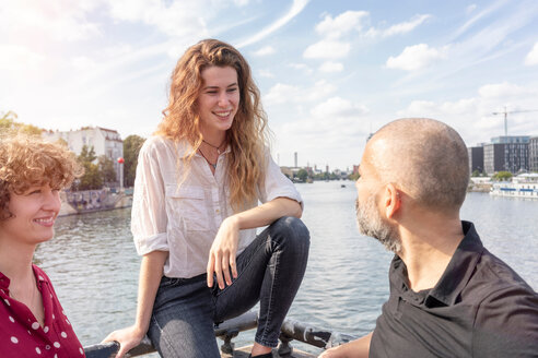 Man and female friends talking, river in background, Berlin, Germany - CUF49954