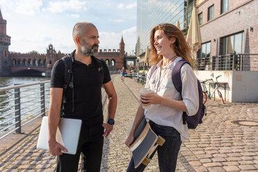Man talking to female friend with skateboard on bridge, river, Oberbaum bridge and buildings in background, Berlin, Germany - CUF49963