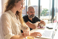 Two entrepreneurs using laptop and having coffee in office - CUF49966