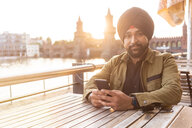 Indian man using smartphone in cafe by river, Berlin, Germany - CUF49984