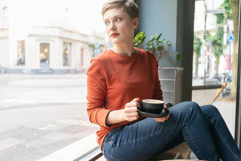 Woman drinking coffee inside shop, Cologne, Nordrhein-Westfalen, Germany - CUF49996