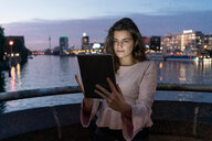 Young woman using digital tablet on bridge, river and city in background, Berlin, Germany - CUF49999