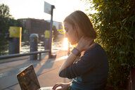 Young woman using laptop outside cafe, Berlin, Germany - CUF50005