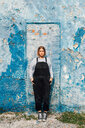 Portrait of woman, weathered wall in background - CUF50047