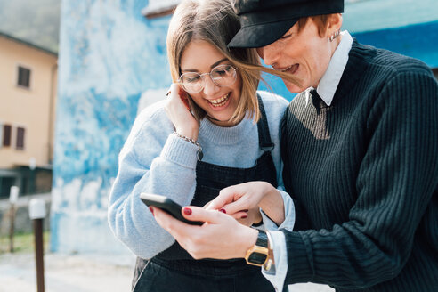 Best friends laughing at text message, Rezzago, Lombardy, Italy - CUF50056