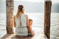 Mother and toddler son sitting on pier, rear view, Lake Orta, Piemonte, Italy - CUF50073