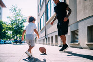 Father and son playing with rugby ball on sidewalk - CUF50100