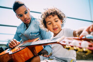 Father teaching son play guitar on stairway - CUF50136