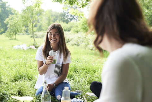 Happy young woman drinking juice with friends at a picnic in park - IGGF00992