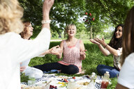 Happy women throwing berries in the air at a picnic in park - IGGF00995