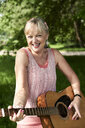 Portrait of happy senior woman playing guitar in park - IGGF01007