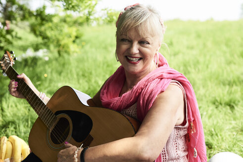 Portrait of happy senior woman playing guitar in park - IGGF01010
