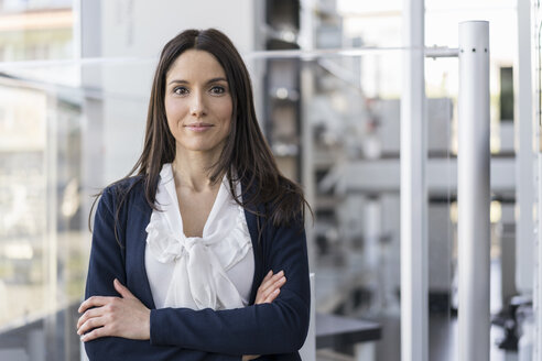 Portrait of smiling businesswoman in a modern factory - DIGF06548