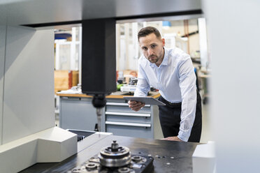 Portrait of businessman with tablet at a machine in a modern factory - DIGF06692