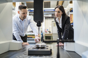 Businessman and businesswoman talking at a machine in modern factory - DIGF06695