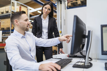 Businessman and businesswoman talking at computer in modern factory - DIGF06698