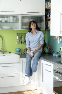 Mature woman with cup of coffee sitting on kitchen counter at home - FLLF00089